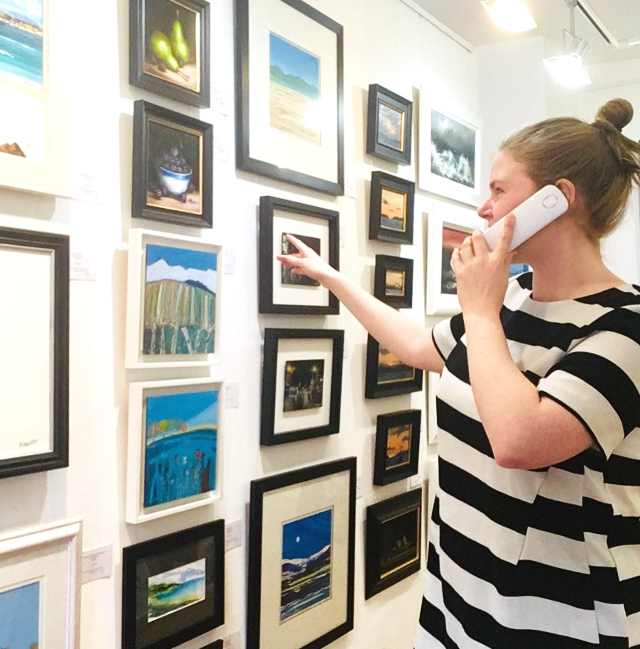 Art gallery assistant in Scotland art gallery on phone to a customer discussing wall of paintings